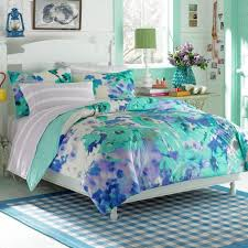 bedroom blue and purple bedding set on the bed and blue rug on the floor