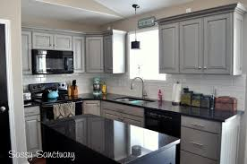 gray-painted-kitchen-cabinets-with-black-appliances-granite-