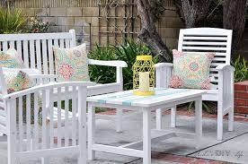 diy outdoor coffe table in patio with white patio chairs and yellow lantern