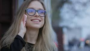attractive young business woman with gles talking on a mobile phone in city 4k stock