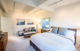 bedroom staging. From The Other Side Of Bed, We Can See Small Seating Area In Bedroom Staging