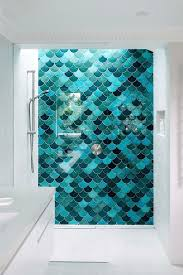 a bright statement wall made of fish scale tiles of diffe shades of turquoise