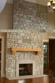 Interior. beige stone fireplace with beige Fireplace Base and brown wooden  mantel shelf . Rustic