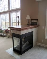 three sided fireplace with tile surround and oak mantle top
