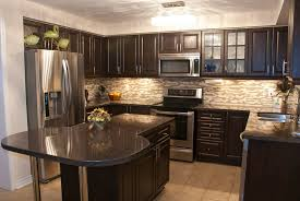 cozy kitchen is stuffed with dark wood cabinetry with brushed metal  hardware black marble