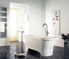 bathroom white freestanding bathtub complete with curved stainless steel faucet on brown tile floor