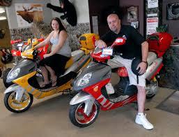 vansant motorsports owner john vansant and his daughter shandell sit on roketa motor scooters at their