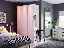a large bedroom with a white wardrobe with light pink doors combined with a bed and bedroom furniture in ikea