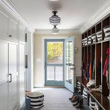 long country style mudroom with open lockers and striped schoolhouse pendants