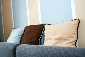 example of throw pillows integrating with the striped wall colors blue white peach brown and sofa pillow arrangement ideas