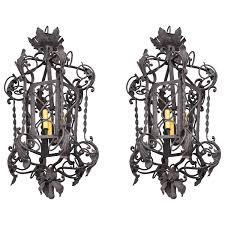 pair of spanish colonial style three light wrought iron chandeliers