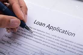 Loan Application Form Close Up Of A Persons Hand Filling Loan Application Form Stock