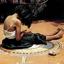 an example of someone sitting in a navajo sand painting for healing purposes