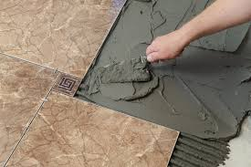 laying ceramic tiles troweling adhesive onto a concrete floor in preparation for laying white floor