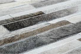 hair detail of a taupe gray cowhide patchwork rug in stripes
