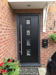 contemporary black posite door in a grey outer frame with 4 central glazed squareodern long bar handle