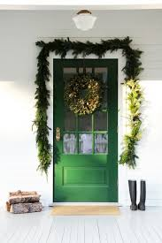 simple festive entry with green painted door fresh garland framing door firewood and winter boots and winter holiday décor inspiration