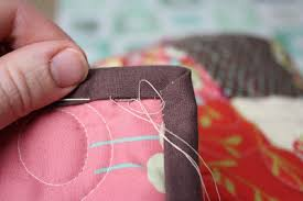 How to bind or finish a quilt & Continue the blind stitch catching down the mitered corner as well. Adamdwight.com