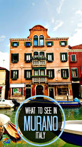 venice c and boat in front of brick colored 4 story house in murano