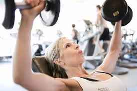 photograph woman lifting free weights in fitness gym by embly