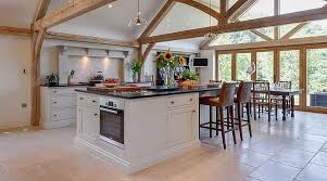limestone tiles kitchen: a beautiful pale country style kitchen with beams and lloyd tumbled limestone flooring by beswick stone