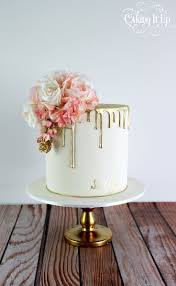 Classy and elegant golden drizzle 60th birthday cake with a pretty posy of  blooms and hand
