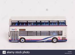 a close up of a toy model double decker bus in first livery on a a close up of a toy model double decker bus in first livery on a white background