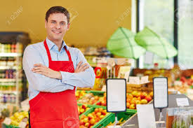 Happy Store Manager In Supermarket With His Arms Crossed Stock Photo