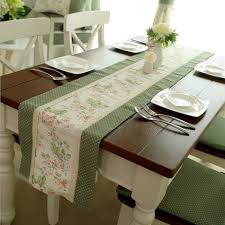 a long white coffee table runner on square wooden table with fl pattern in the middle