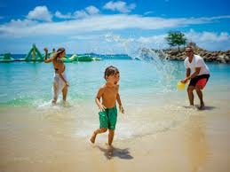 kid splashing with pas on the beach