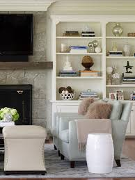 chic living room featuring built in cabinets with beadboard trim flanking tv over stone fireplace