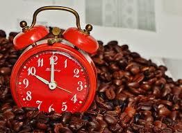 red double bell alarm clock on top of coffee beans