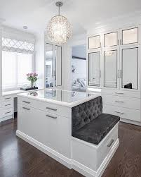 Luxurious walk-in closet boasts an ornate chandelier hung over a mirror top  white center island finished with satin nickel pulls and a built-in bench  topped ...