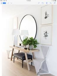 Minimalist entryway with oversized round mirror over light toned table.  From Architectural Digest.