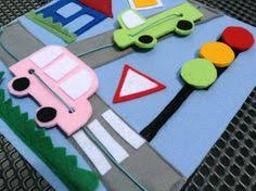 this busy quiet book page made of felt uses strings to move little felt cars