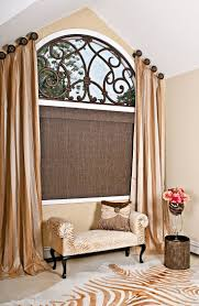 An arched window dressed in a beautiful angled panels, finished with a  custom faux iron piece and a woven woods with silk window shade, gives this  room a ...