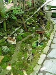 outdoor fairy garden. a working train runs through this miniature village that uses moss to simulate grassy fields. outdoor fairy garden