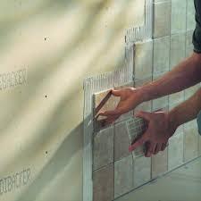 applying mortar to tile a wall