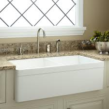 the white baldwin double bowl farmhouse fireclay sink is the perfect fit for a busy kitchen