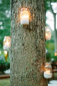 Candles in mason jars on a tree. Great for outdoor parties/wedding. Not a  huge fan of mason jars, but its very cute this way.