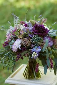 Plum and lavender bridal bouquet featuring dahlias, roses, succulents, and  lots of fragrant