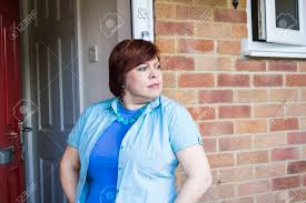 opening front door. Happy Middle Aged Woman Opening Front Door And Smiling Stock Photo - 56635518