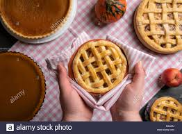 Hands Holding A Tray With An Apple Pie Above A Kitchen Table Full