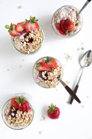 jars filled with overnight oats strawberry jam fresh strawberries and sprinkled with rolled