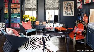 kourtney kardashian fabulous home office with navy blue walls framing navy blue built in bookcases stacked with color blocked books blue home office