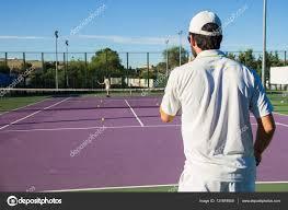 professionele tennisslster spelen van het spel op de tennisbaan hij heeft zijn rug naar de