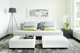 In a small living room, each piece of furniture should earn its keep. Think  of using ottomans that work as a coffee table or extra seating, nesting  side ...