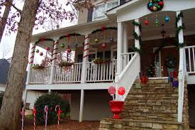 Extra large ball ornaments hang from ribbon on the front porch and candy  canes greet you at the bottom.