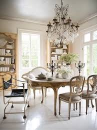 french dining chairs a gilded carved leg oval dining table ivory love seat and oversized crystal chandelier make for a seriously glamorous dining room