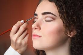 closeup portrait of beautiful woman getting professional make up with brush beauty and makeup